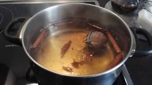 En una olla, hervir a fuego lento el vino, el agua, las ramas canela, el azúcar, y en un infusionador, la corteza de limón y de naranja unos 15 minutos.