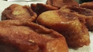 Torrijas recien fritas en una bandeja con papel de cocina.