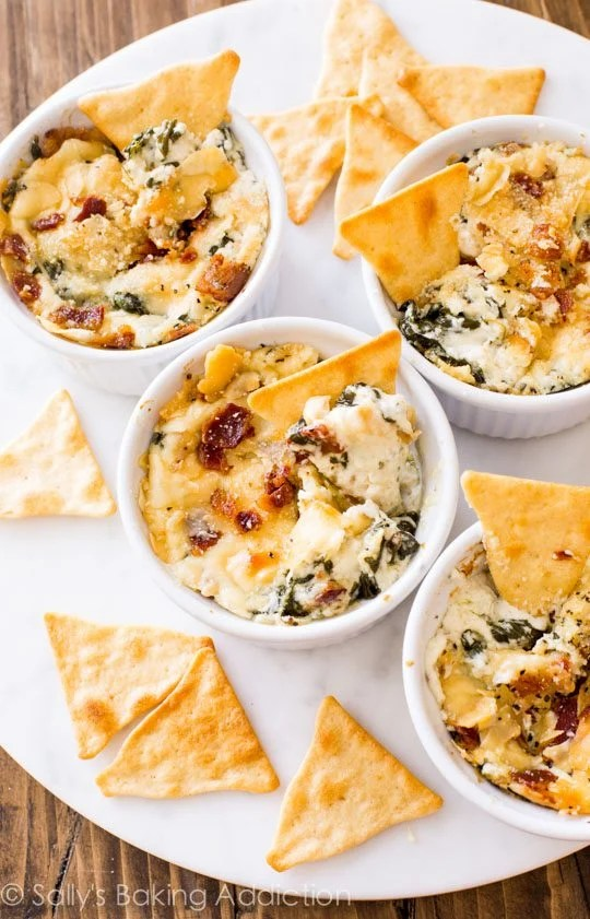Creamy warm spinach dip made with roasted garlic, crispy bacon, and parmesan cheese. This dip was gone in minutes! Recipe on sallysbakingaddiction.com