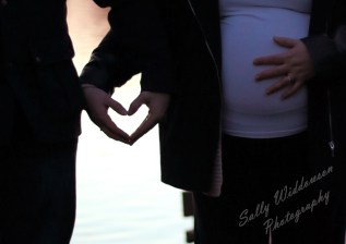 Close up pregnant couple back-lit by sunset make loveheart silhouette with hands for outdoor pregnancy photoshoot