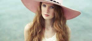 Beautiful woman in hat on the sea. Fashion photo