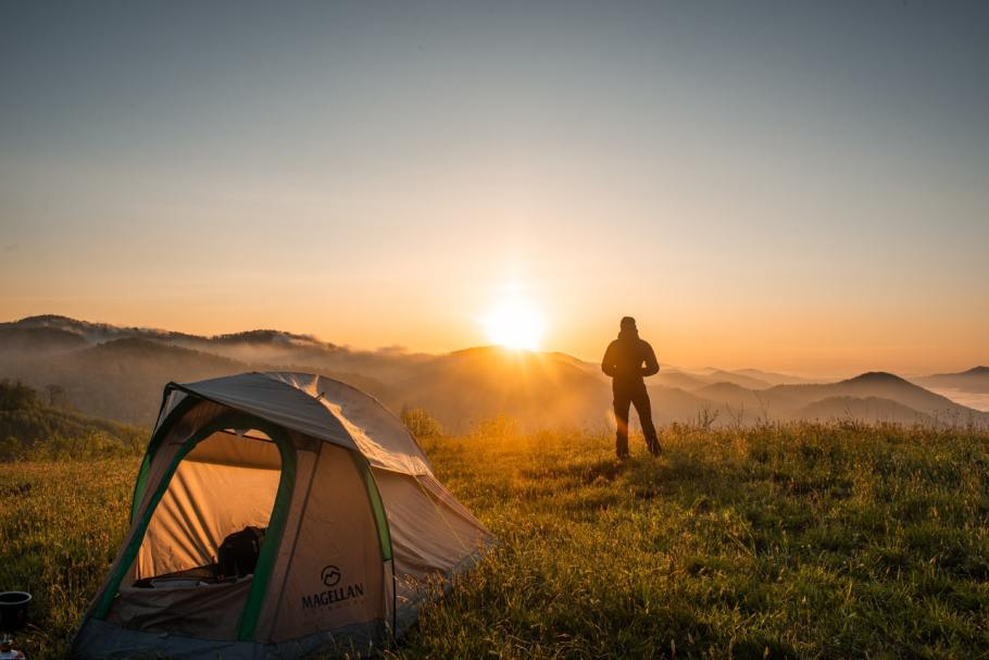 silhouette of person standing near camping tent 2398220