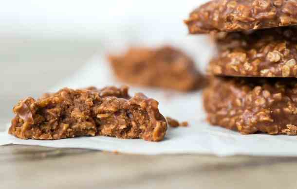 A close up of a chocolate peanut butter oatmeal cookie, with a bite taken out of it.