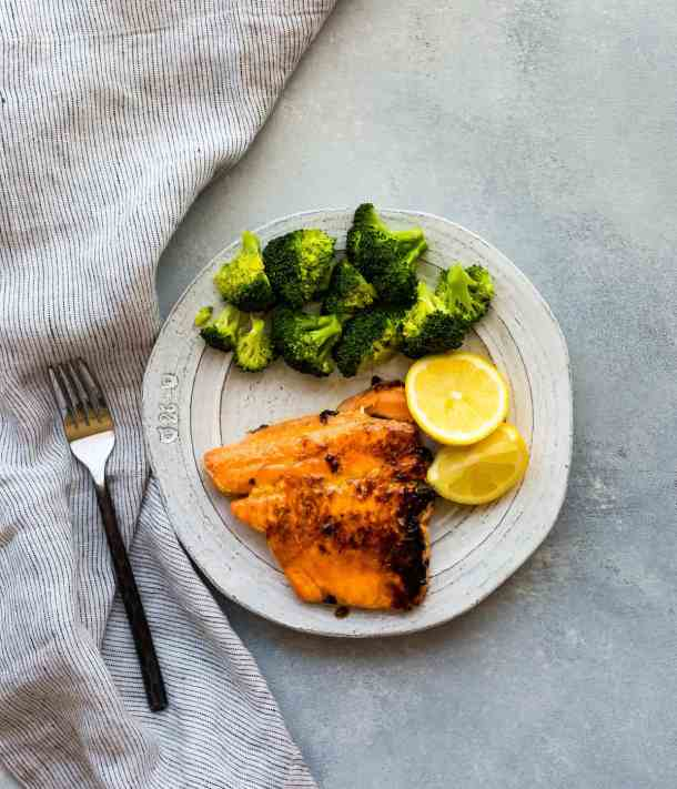 A salmon fillet, two lemon wedges, and a small pile of broccoli sitting on a white plate.