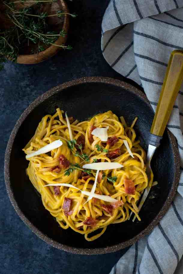 Butternut squash Alfredo pasta piled into a small black bowl. A muted striped colored napkin sits next to the bowl.