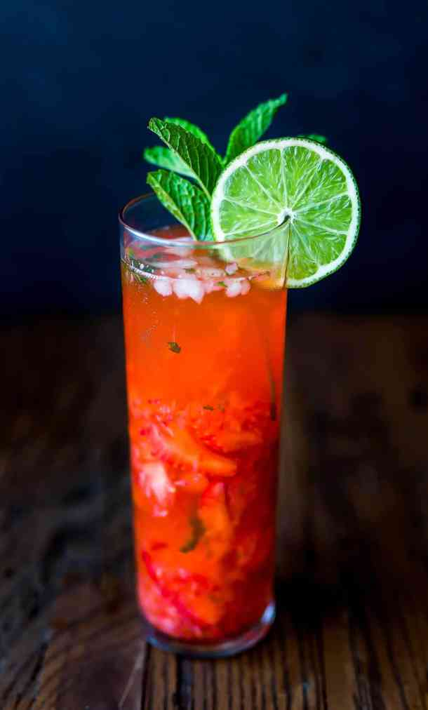 Virgin strawberry lime mojito with a lime wedge on the rim of the glass.