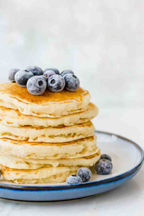 Fluffy homemade buttermilk pancakes from scratch, topped with frozen blueberries.