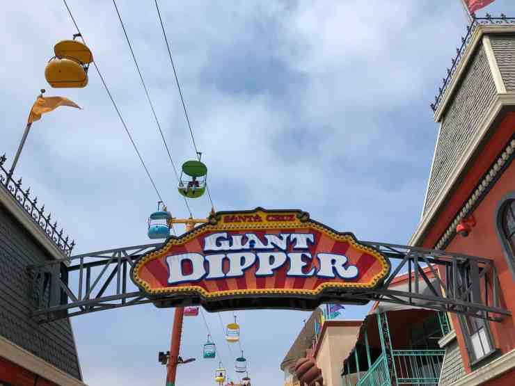 giant dipper sign at the santa cruz beach boardwalk with brightly colored gondolas soaring above