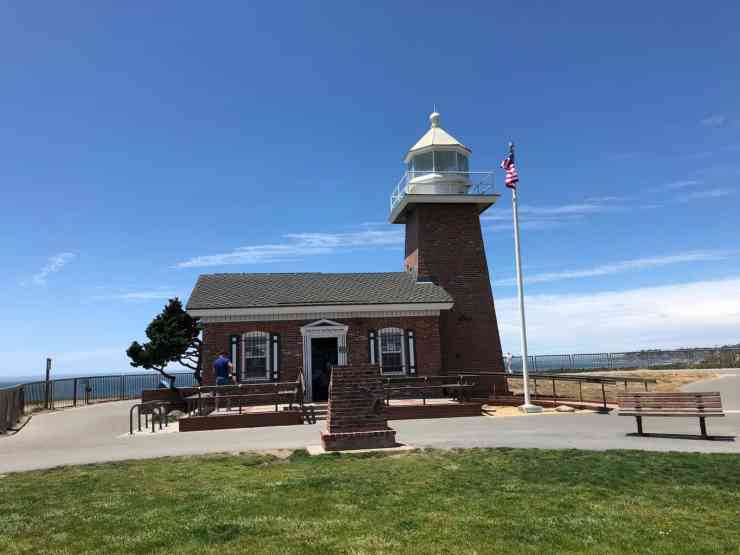 small brick lighthouse with a lawn in front and the ocean in the background in santa cruz, CA