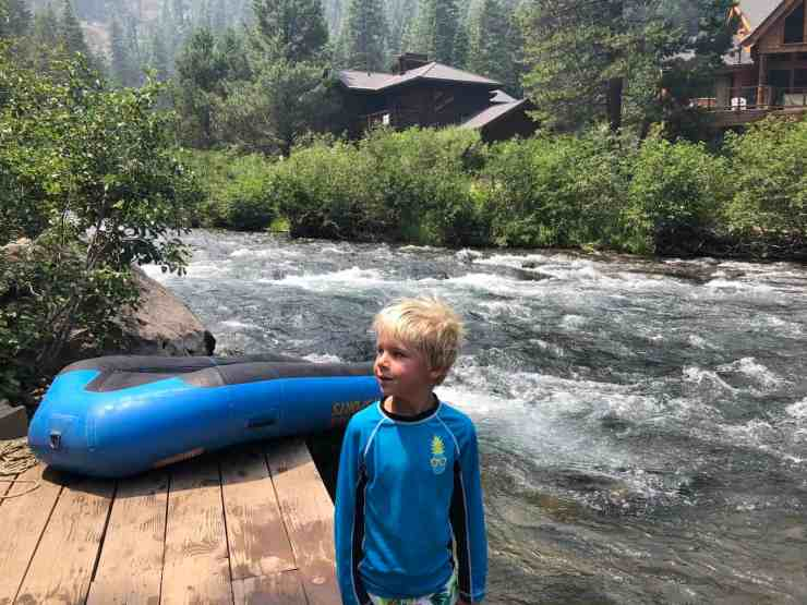 boy standing next to a river raft alongside the Truckee river in Lake Tahoe, California
