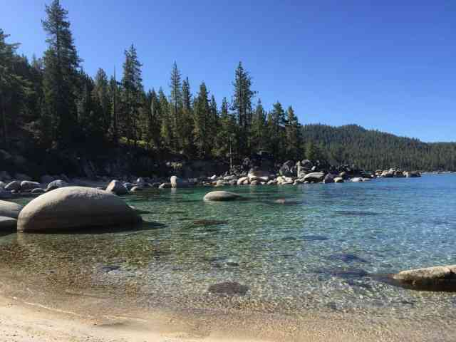 big boulders in a clear blue-green colored lake. swimming in the lake is a must when you're in lake tahoe with kids