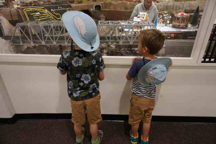 Two little boys with matching blue hats looking at an exhibit in the model train museum