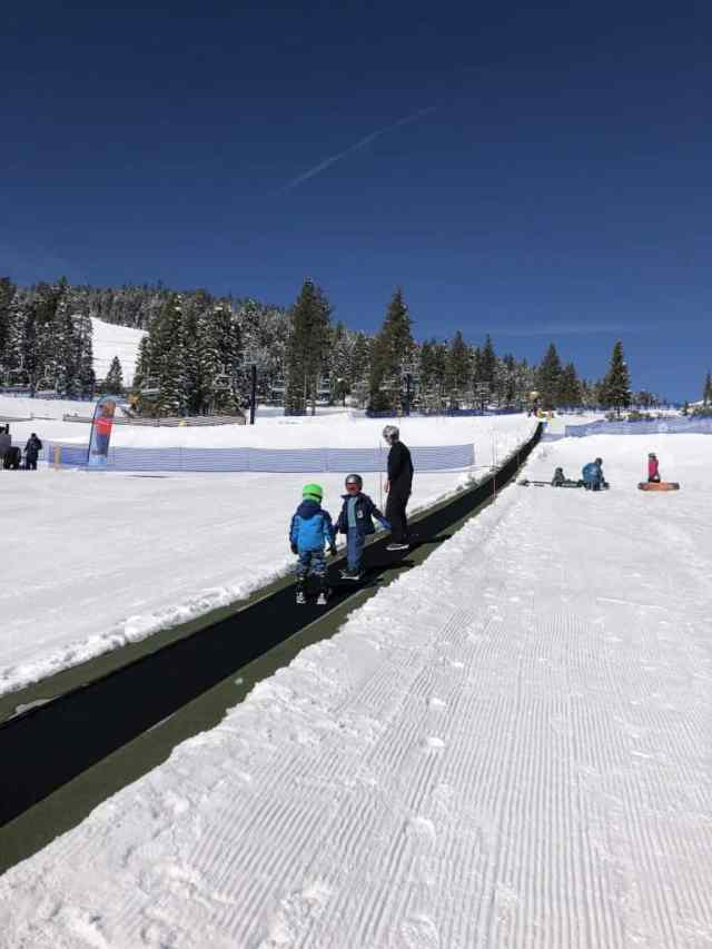 dad and sons on a conveyor belt going spa small ski hill. northstar is one of the best places in lake tahoe to ski with kids or adults who are learning