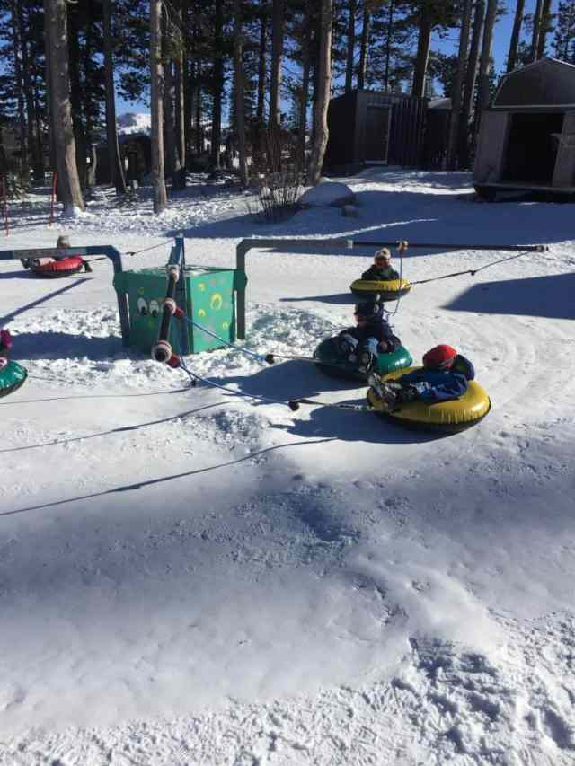 toddlers in inner tubes on a snowy ride