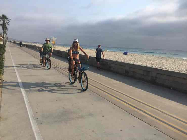 family riding beach cruisers along mission beach in san diego. this is a very fun thing to do in San Diego with kids or without!