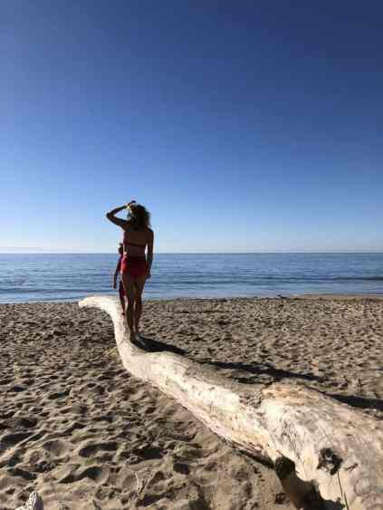 woman in red swimsuit walking on a piece of driftwood at the beach facing the ocean. Hanging out at the beach is my one of favorite things to do in santa cruz!
