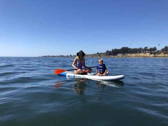 mom in a purple swim suit and toddler in a life jacket on a paddle board in the ocean