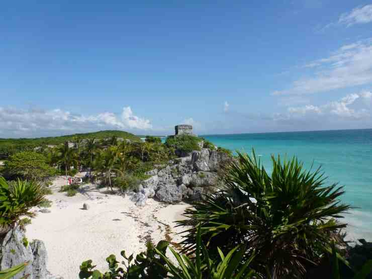 a sandy cove with the tulum ruins on the cliff above in mexico. Tulum is a great option when you're trying to decide between Hawaii or Mexico