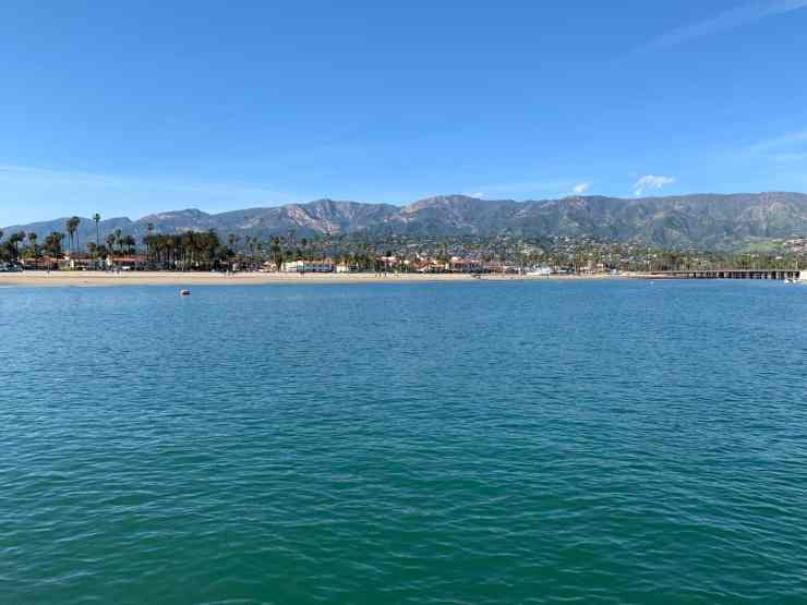Santa Barbara coastline from a boat. blue ocean, beach, and mountains in the distance.