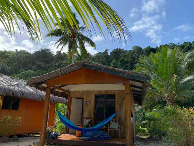 A small cabana with tropical mountains behind it and a blue hammock hanging on the porch. A travel hammock is a great gift for travelers or families who love the outdoors