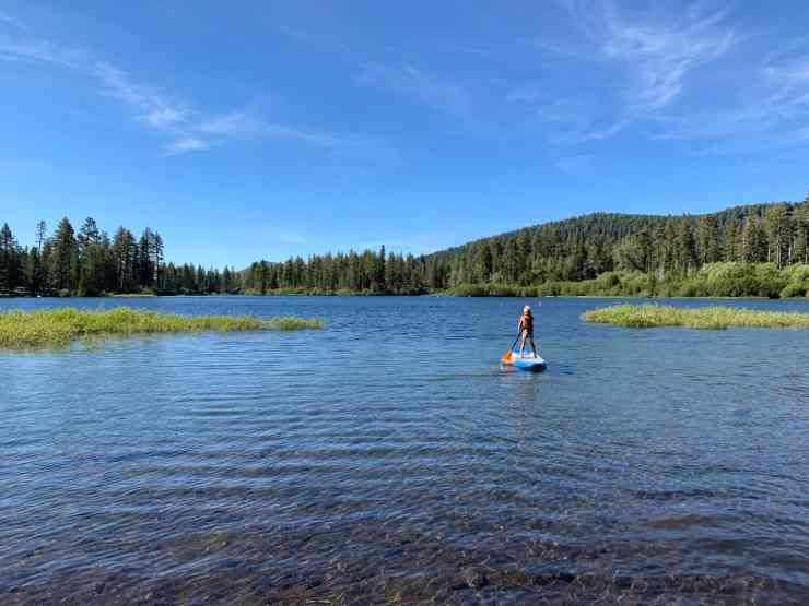 Little boy paddling a SUP on an alpine lake. A day at Manzanita Lake is one of the best things to do in Lassen National Park with kids