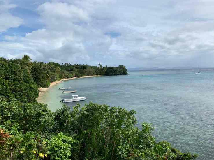tramonte in taveuni fiji overlooks a tropical bay with a few fishing boats anchored in it.