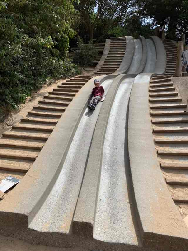 A boy sliding down a slide made of cement at Koret Playground in Golden Gate Park