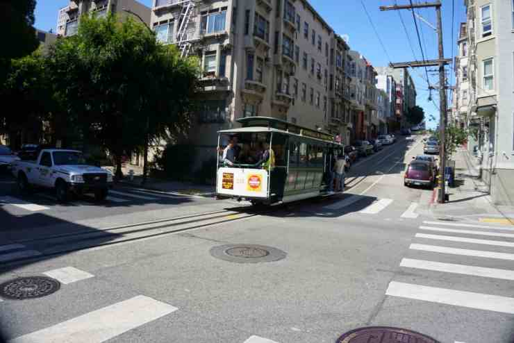 A cable car heading up a rolling hill in San Francisco, CA. Taking a cable car ride is a great way to see the city on a long layover in San Francisco