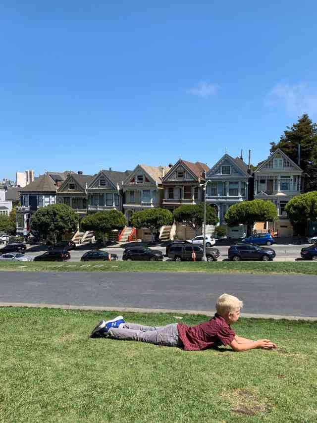A boy getting ready to roll down a grassy hill in Alamo Square in San Francisco, CA.