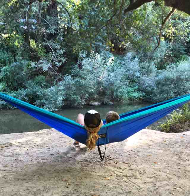 Mom and son sitting in a hammock next to a river. Giving someone a travel hammock is a eco-friendly gift that will provide endless hours of happiness