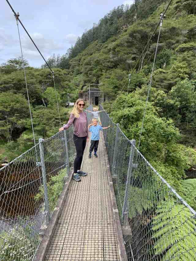 The Windows Walk on the North Island of New Zealand is one of the best short hikes in New Zealand for kids. Mom and two boys standing on a suspension bridge