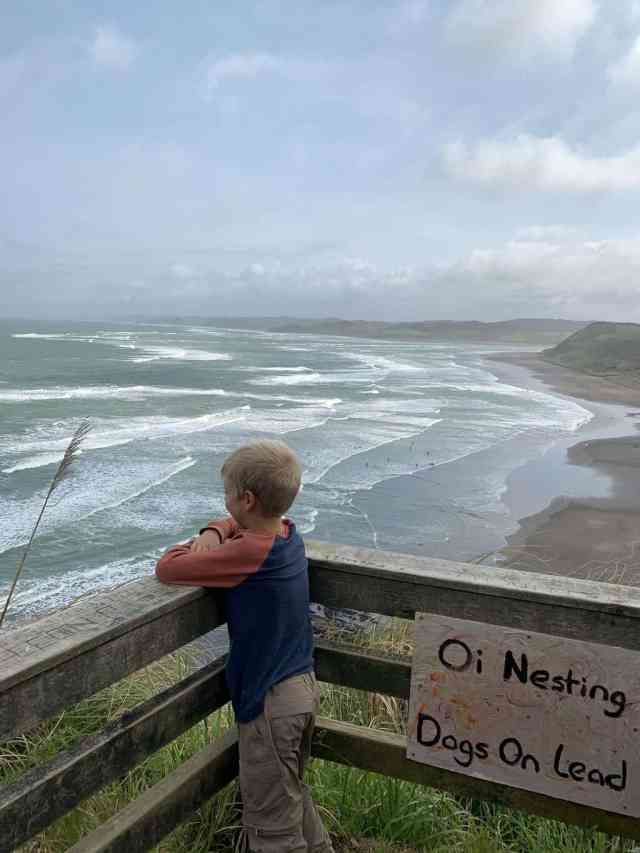 Boy looking down at the beach in Raglan from the cliff.