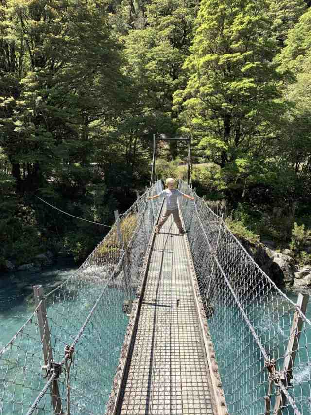 Lake Marian track is a challenging hike near Milford Sound but the bottom section is fairly easy and beautiful. Boy standing on a suspension bridge over aqua blue river