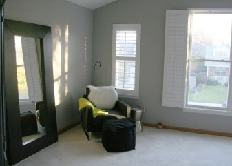 A small reading nook with a soft upholstered chair and ottoman create another cozy space within the master suite