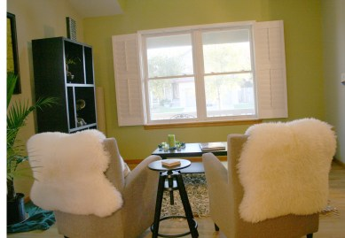 Large plantation shutters along with smaller side chairs create a cozy inviting sitting area.
