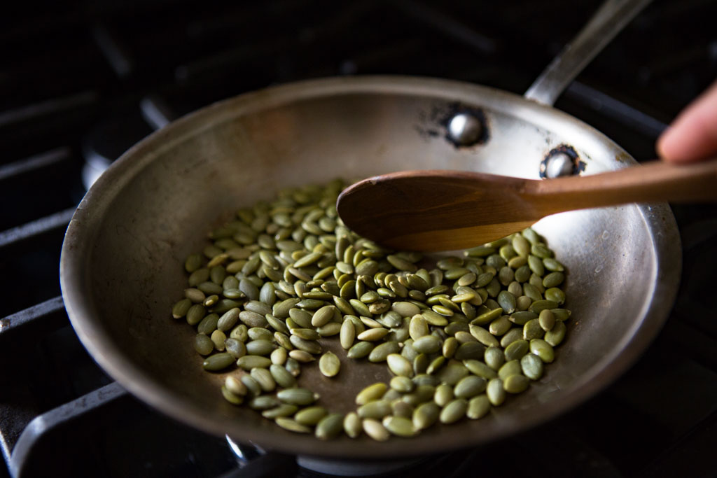 Toast pumpkin seeds in a small pan until they pop and remove from heat.