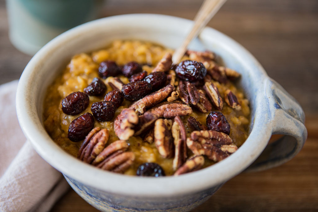 Creamy smooth Slow Cooker Pumpkin Spice Oatmeal with craisens and pecans.
