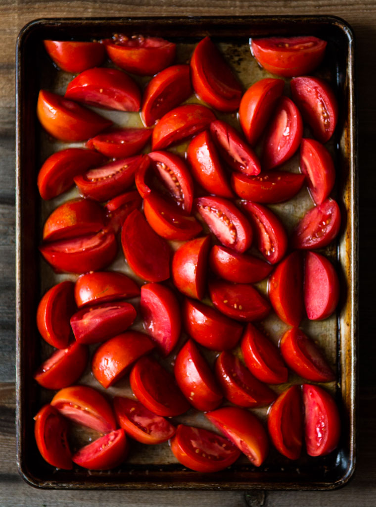 Sliced tomatoes on a sheet pan ready to be roasted.