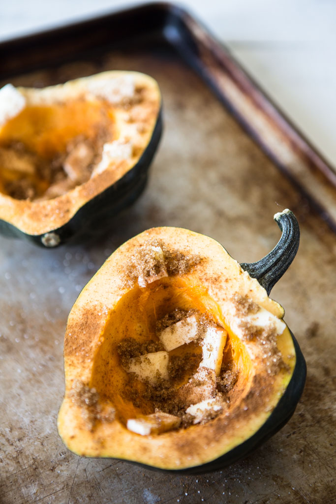 Sliced acorn squash with brown sugar, butter and cinnamon ready for making Protein-Packed Acorn Squash Boats.