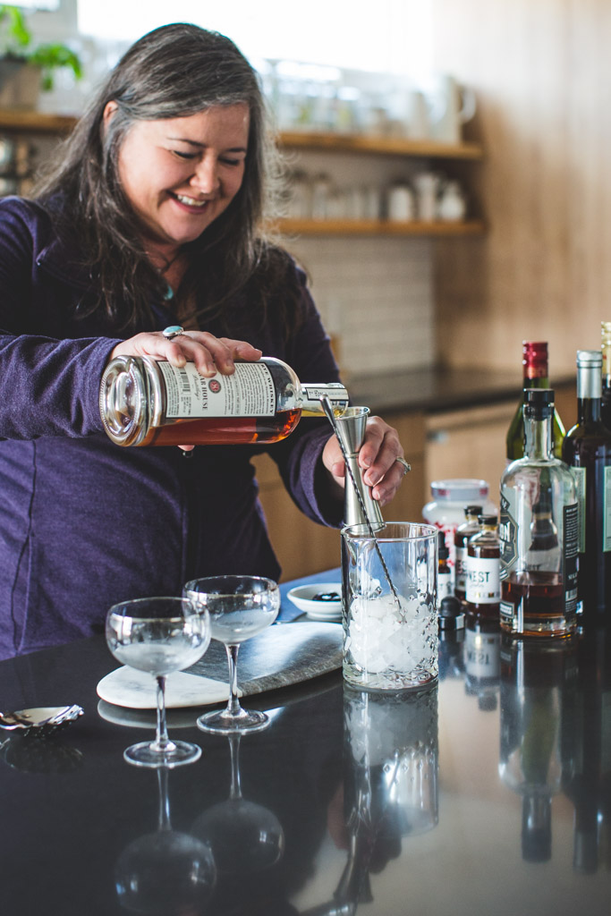 Darby Doyle, aka a Bourbon gal, mixing up Manhattans in her home bar.