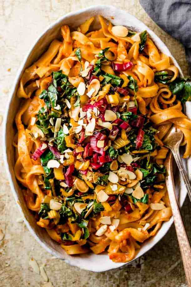 This tuscan pasta feast is a healthy and quick way to get extra veggies this winter. Rich roasted red peppers pasta with bitter wilted Italian green and toasted almonds.