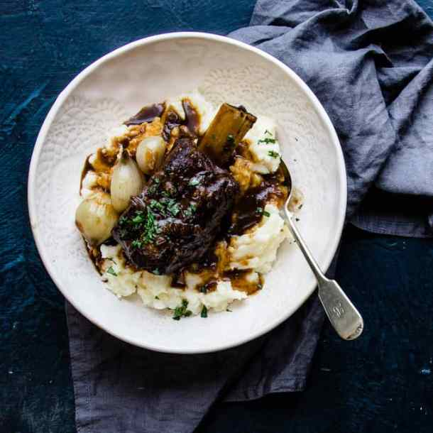 These slow cooker beer braised beef short ribs are a cozy fall off the bone winter classic. Tender, melting beef, dark micro brew ale mixed with spices and savoury beef stock are the perfect winter warmer. They're a no maintenance dinner that is perfect for freezing ahead of a busy week. #beef #shortribs #winter #dinner #makeaheadfreezer #mealprep