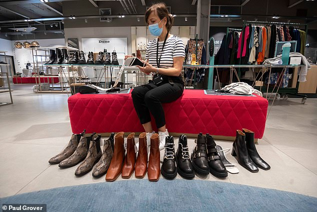 A John Lewis staff member cleans shoes at their store in White City ahead of non-essential shops reopening next Monday