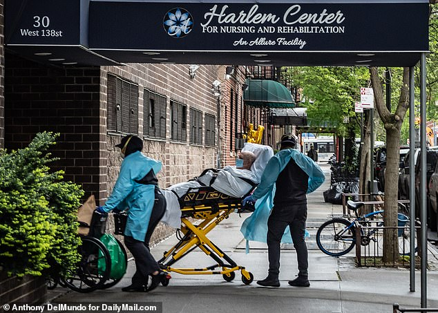 Medical workers attend to a patient outside Harlem Center for Nursing and Rehabilitation where at least 20 bodies had been seen removed during coronavirus pandemic despite state data only showing five COVID-19 deaths last May