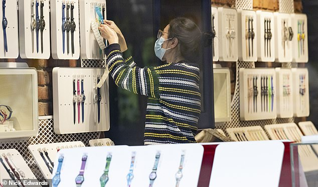 A worker at Swatch on Oxford Street hangs a watch on a holder yesterday as the store prepares to welcome shoppers back
