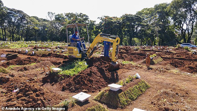 A grave digger works on a plot of land near Sao Paulo in Brazil where people who have died of Covid are being buried