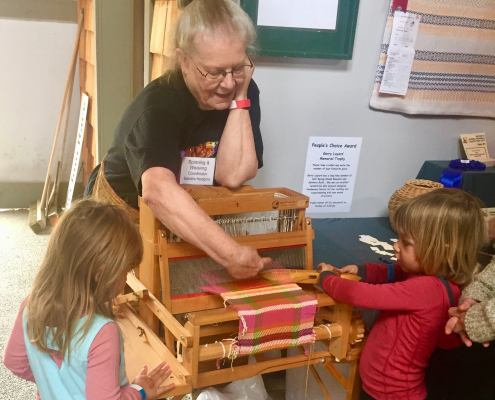 two young girl learning to weave under the guidance of Sandra