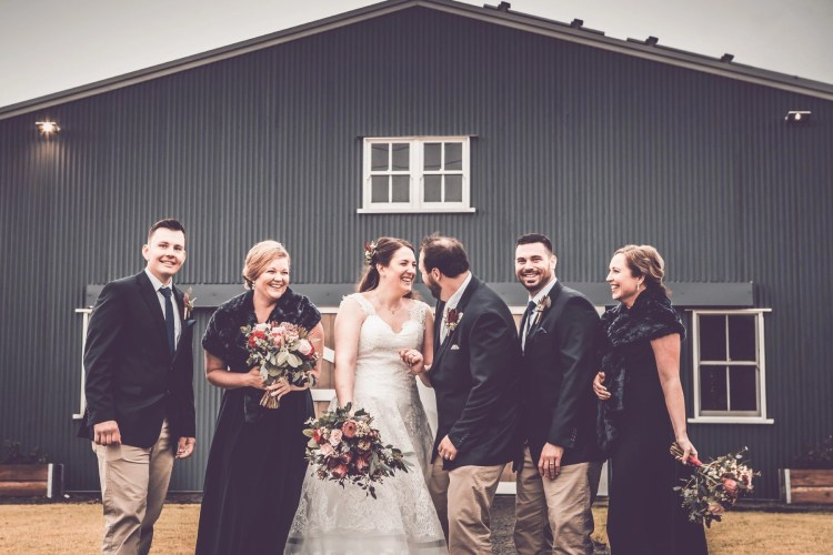 Bridal party laughing barn cloudy weather winter