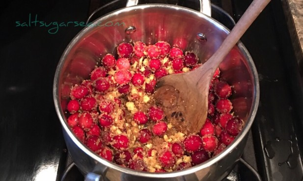 Whole fresh cranberries cooking on the stove with ginger, sugar, and pineapple