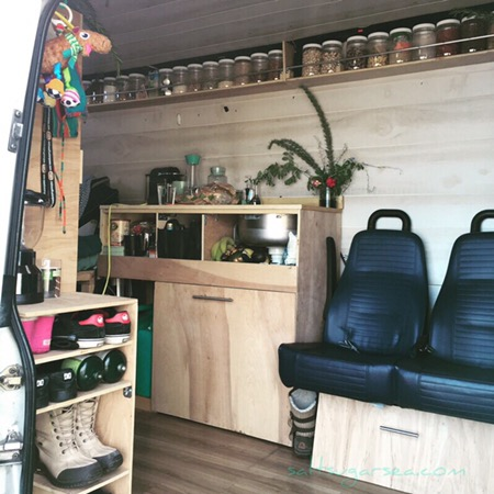 Van Conversion view inside with bus seats facing sideways, dry goods floating shelf with jars, kitchen sink and shoe each made from wood